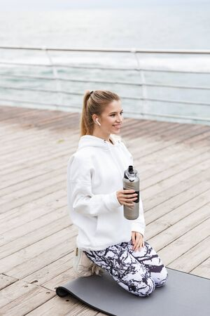 Attractive smiling young sportswoman wearing hoodie sitting on a fitness mat outdoors at the beach, listening to music with earphones, holding water bottle