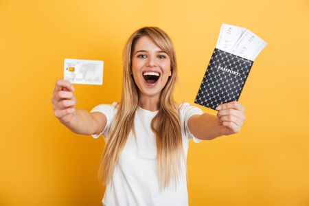 Image of emotional positive young blonde woman jumping isolated over yellow wall background dressed in white casual t-shirt holding passport with tickets and credit card.