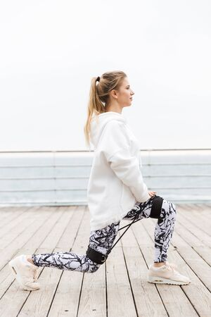 Attractive confident young sportswoman wearing hoodie working out outdoors at the beach, exercising with expander 写真素材