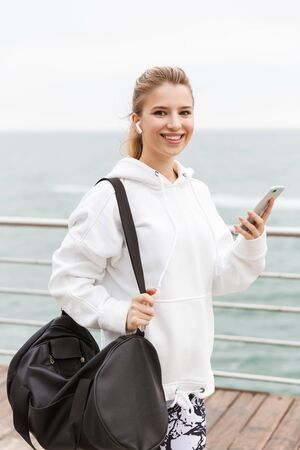 Image of happy young woman 20s in white hoodie using cellphone and earpods while walking near seaside with sporty bag Stock Photo