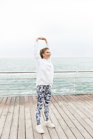 Attractive young sportswoman wearing hoodie working out outdoors at the beach, doing stretching exercises