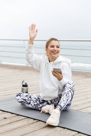 Image of sporty smiling woman 20s in white hoodie holding smartphone and waving hand while sitting on fitness mat near seaside