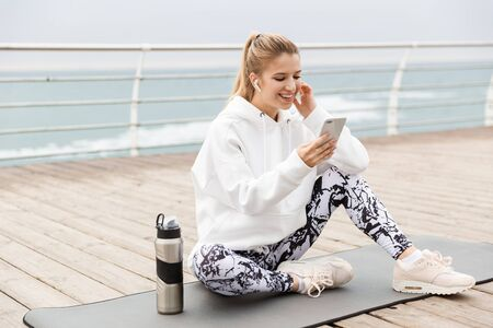 Attractive smiling young sportswoman wearing hoodie sitting on a fitness mat outdoors at the beach, using mobile phone while listening to music 스톡 콘텐츠