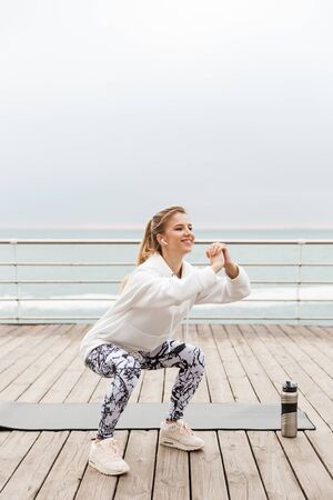 Attractive smiling young sportswoman wearing hoodie working out with fitness mat outdoors at the beach, doing squats