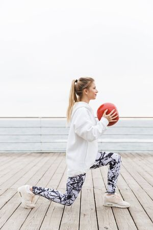 Attractive confident young sportswoman wearing hoodie working out outdoors at the beach, squatting with medicine ball