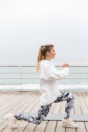 Attractive smiling young sportswoman wearing hoodie working out with fitness mat outdoors at the beach, doing lunges