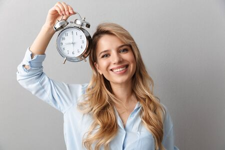 Photo of caucasian blonde woman 20s dressed in shirt smiling while holding alarm clock isolated over gray background Stock Photo