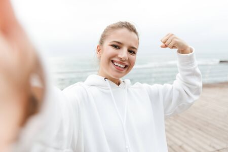 Image of pretty nice woman 20s in white hoodie taking selfie photo and showing her bicep while walking near seaside