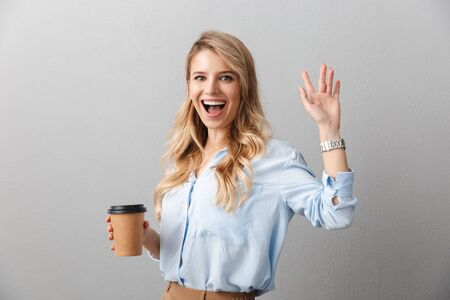 Attractive young blonde businesswoman wearing shirt standing isolated over gray background, holding takeaway coffee cup, waving hand