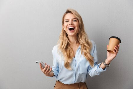 Attractive young blonde businesswoman wearing shirt standing isolated over gray background, holding takeaway coffee cup, holding mobile phone, celebrating