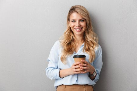 Attractive young blonde businesswoman wearing shirt standing isolated over gray background, holding takeaway coffee cup, looking at camera