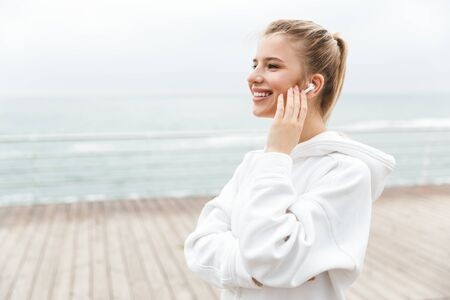 Image of happy nice woman 20s in white hoodie smiling and listening to music with earpods while walking near seaside Stock Photo