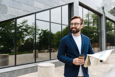 Portrait of happy businessman wearing eyeglasses drinking coffee from paper cup and reading newspaper while standing outdoors near building