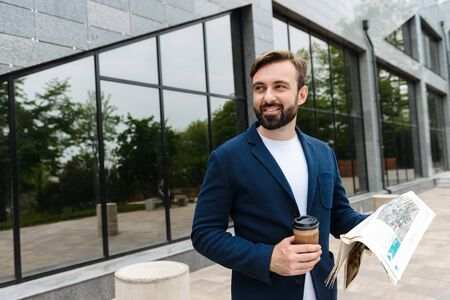 Portrait of joyful businessman in jacket drinking coffee from paper cup and reading newspaper while standing outdoors near building