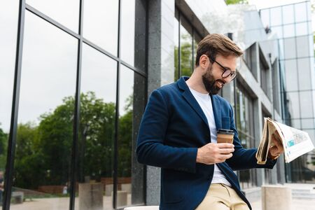 Attractive smiling young bearded man wearing jacket reading newspaper while standing outdoors at the city and drinking takeaway coffee