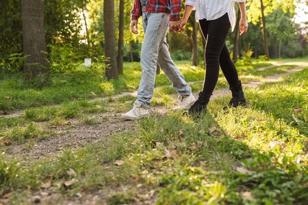 Cropped picture of a young loving couple walking outdoors in a green nature park forest.