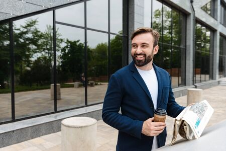 Portrait of cheerful businessman in jacket drinking coffee from paper cup and reading newspaper while standing outdoors near building
