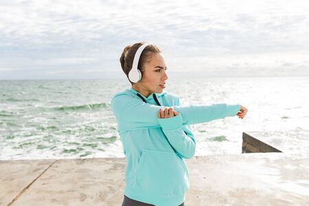 Attractive confident healthy fitness woman wearing headphones exercising outdoors at the beach, stretching hands