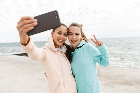 Two happy young fitness women wearing hoodies taking a selfie while stading at the beach, showing peace gesture Banco de Imagens