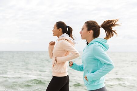 Side view of two beautiful confident young fitness women jogging outdoors, along seashore
