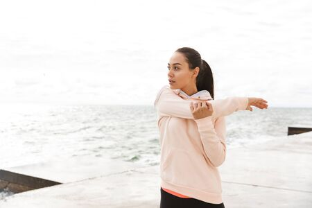 Confident young fitness asian woman exercising at the beach, stretching Banco de Imagens
