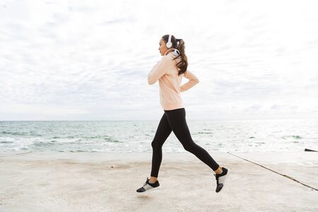 Full length side view of an attractive young asian fitness woman jogging at the beach, listening to music with headphones Imagens