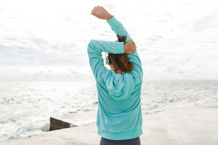 Back view of a healthy fitness woman wearing headphones exercising outdoors at the beach, stretching hands 版權商用圖片