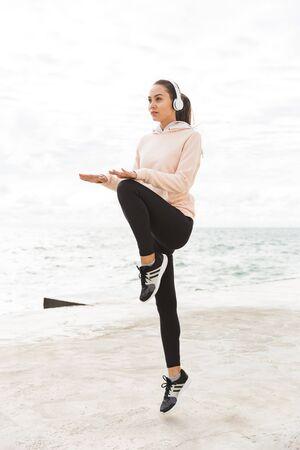 Attractive young asian sportswoman exercising at the seashore, wearing headphones, jumping Banco de Imagens