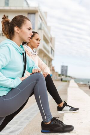 Two attractive confident young fitness women wearing hoodies exercising outdoors at the seashore, doing stretching exercises Banco de Imagens