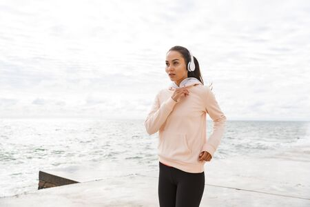 Attractive young asian fitness woman jogging at the beach, listening to music with headphones
