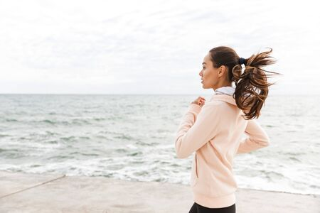 Attractive young asian sportswoman exercising at the seashore, running, wearing headphones