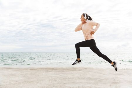 Attractive young asian sportswoman exercising at the seashore, running, wearing headphones Stok Fotoğraf - 128714255
