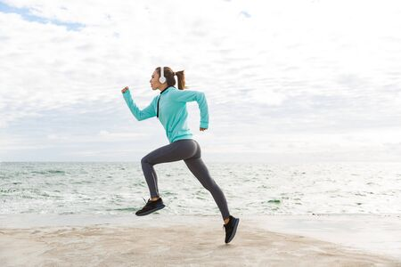 Attractive confident healthy fitness woman wearing headphones exercising outdoors at the beach, running Banco de Imagens