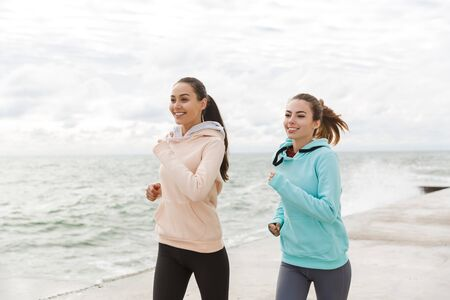 Two beautiful smiling young fitness women jogging outdoors, along seashore