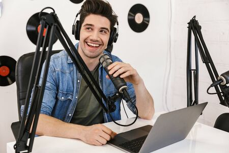 Happy young man radio host broadcasting through microphone in studio, using laptop computer