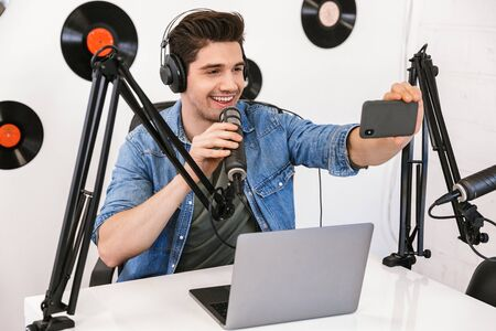 Image of a handsome young man radio host at the workspace with microphone and sound equipment take selfie by mobile phone.
