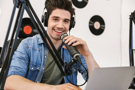 Happy young man radio host broadcasting through microphone in studio, using laptop