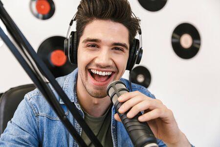 Happy young man radio host broadcasting through microphone in studio Stock Photo