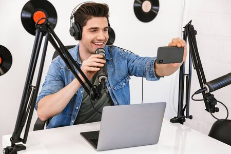 Handsome happy young male radio host broadcasting in studio, using microphone and headphones, taking a selfie