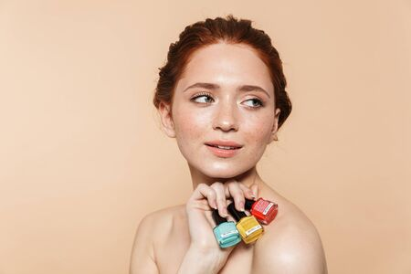 Beauty portrait of an attractive young redhead woman standing isolated over beige background, showing nail polish