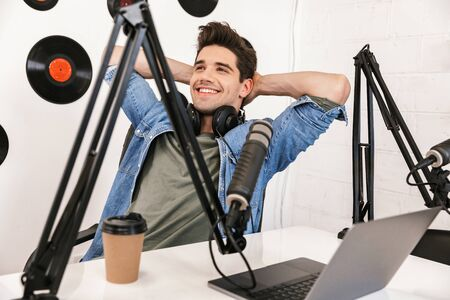 Handsome happy young male radio host broadcasting in studio, using microphone and headphones 版權商用圖片
