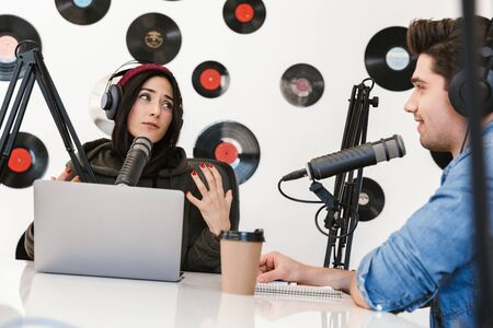 Image of a handsome young man radio host with colleague woman at the workspace with microphone and sound equipment talking with each other. 版權商用圖片