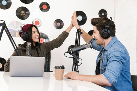 Image of a handsome young man radio host with colleague woman at the workspace with microphone and sound equipment talking with each other give a high-five.