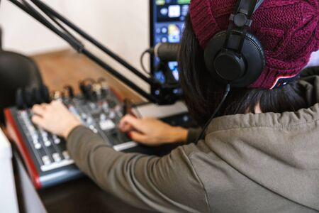 Close up of a young female radio host broadcasting in studio, using computer and headphones