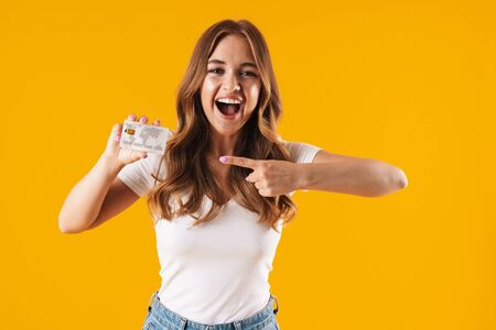 Photo of lovely young woman rejoicing while holding and pointing finger at credit card isolated over yellow background Imagens