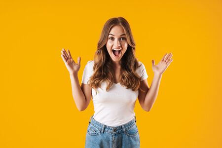 Excited young girl wearing casual clothes standing isolated over yellow background, celebrating success