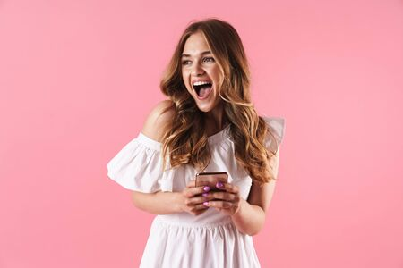 Beautiful excited young blonde girl wearing summer dress standing isolated over pink background, using mobile phone