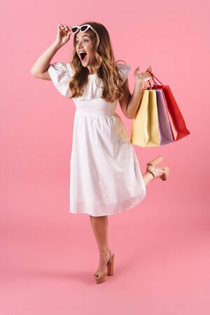 Image of beautiful amazed woman wearing white dress holding shopping bags and sunglasses isolated over pink background 版權商用圖片