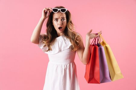 Image of beautiful shocked woman wearing white dress holding shopping bags and sunglasses isolated over pink background