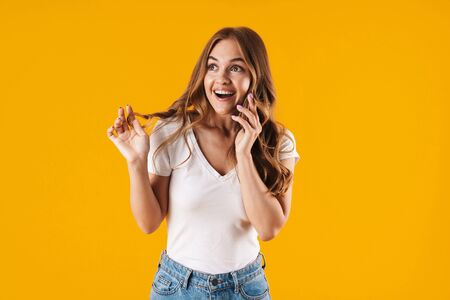 Portrait of a cheerful young casual girl standing isolated over yellow background, talking on mobile phone